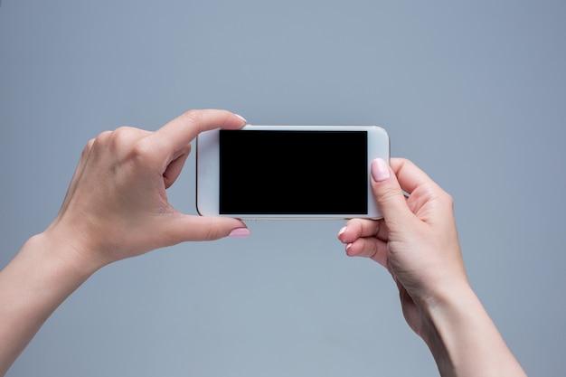 灰色の背景に携帯電話で入力する女性のクローズアップショット。現代のスマートフォンを押しながらイチジクで指している女性の手。空白の画面で自分のwebページまたはメッセージに配置します。