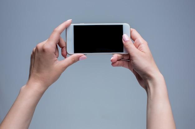 회색 바탕에 휴대 전화에 입력하는 여자의 근접 촬영 샷. 현대 스마트 폰 들고 손가락으로 가리키는 여성 손.