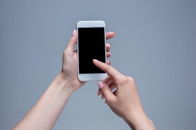 Снимок крупным планом женщины, печатающей на мобильном телефоне