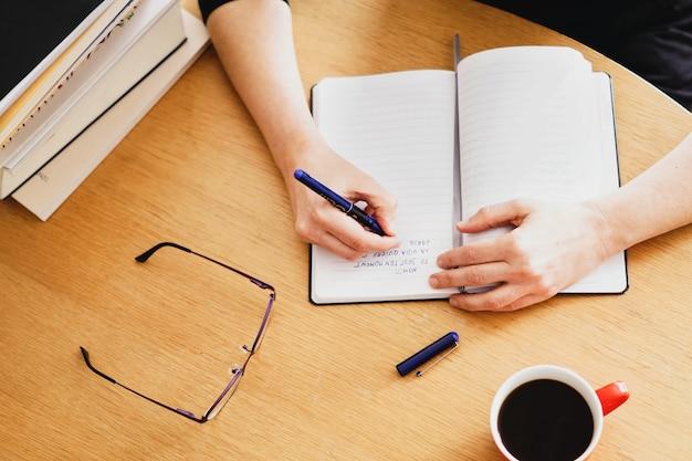 近くに赤いコーヒーカップを持って自宅で働いている、または勉強している女性のクローズアップショット