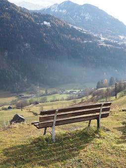 Снимок крупным планом деревянной скамейки с большой горой