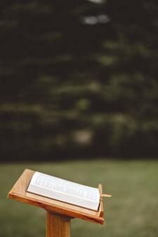 Крупным планом выстрелил деревянный стенд речи с раскрытой книгой