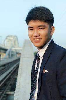 다리에 서서 웃고 소송에서 젊은 아시아 남자의 근접 촬영 샷