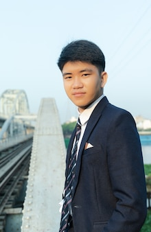 橋の上に立っているスーツの若いアジア人のクローズアップショット