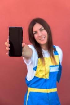 彼女のスマートフォンがカメラにポーズをとって若い女性のクローズアップショット