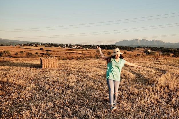 Снимок крупным планом молодой девушки в круглой шляпе, идущей в поле