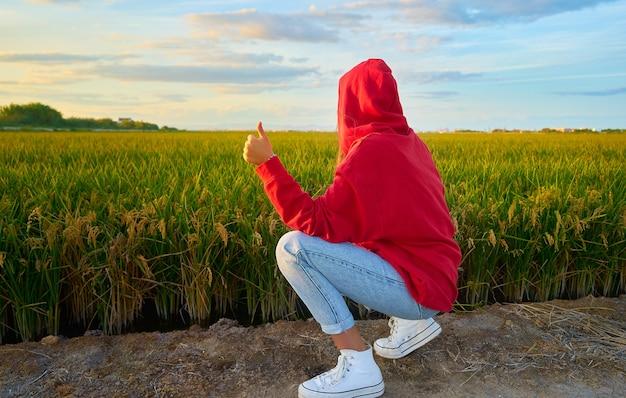 Крупным планом снимок молодой женщины в красном, весело рядом с зеленым полем в солнечный день