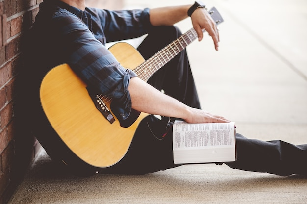 Снимок крупным планом молодого мужчины, сидящего с книгой и гитарой в руках