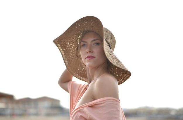 澄んだ空の下で帽子をかぶっている若い女性のクローズアップショット