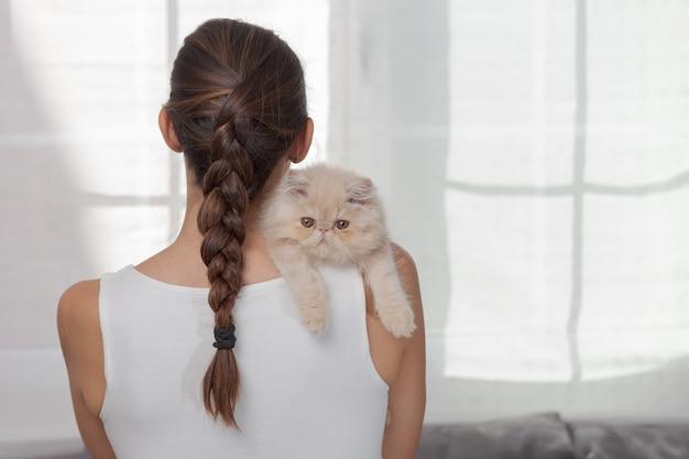 Снимок очаровательной домашней кошки на плече крупным планом