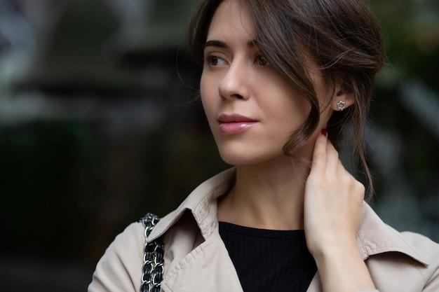 愛らしい若い女性のクローズアップショットは流行のコートを着ています
