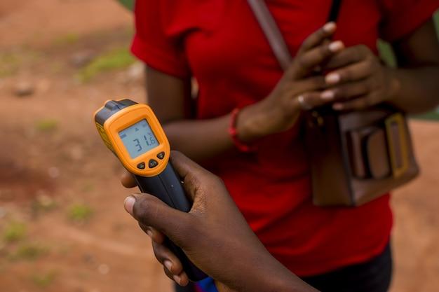 ハンドヘルド赤外線温度計を保持しているアフリカの女性のクローズアップショット