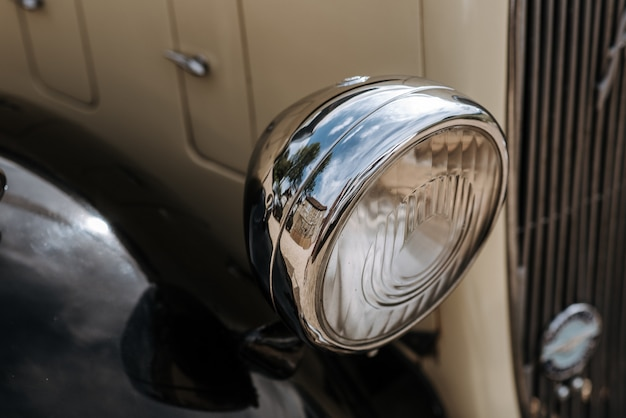 アンティークの白い車のヘッドライトのクローズアップショット