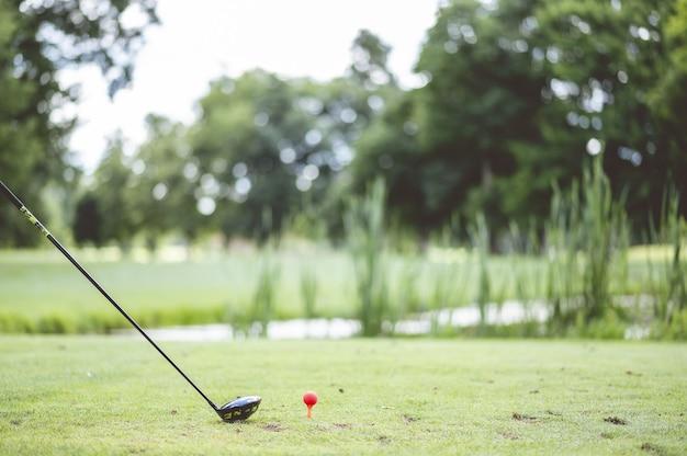 잔디 덮인 코스에서 골프 클럽과 골프를 치는 선수의 근접 촬영 샷