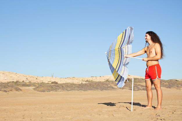 Снимок крупным планом привлекательного молодого человека с длинными вьющимися волосами, поправляющего зонтик на пляже
