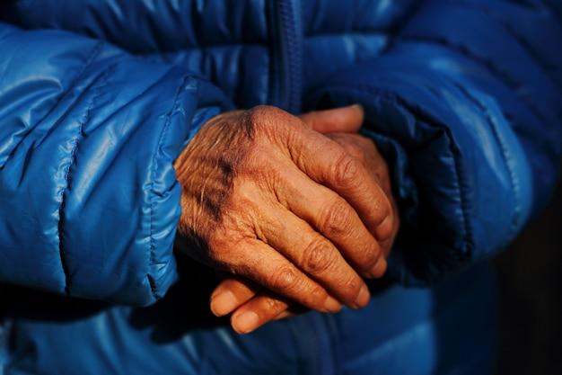 高齢者の女性のしわだらけの手のクローズアップショット