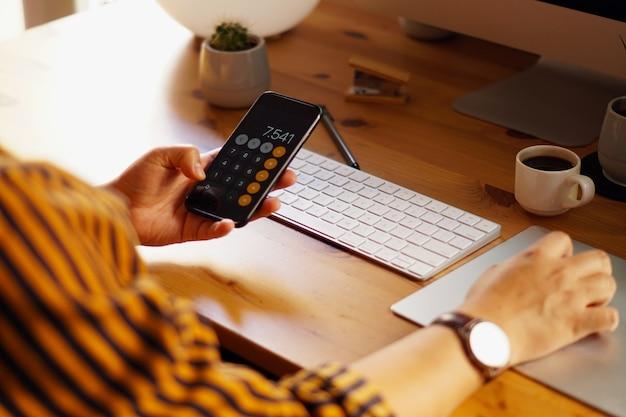 自宅で仕事をし、計算をしている起業家のクローズアップショット