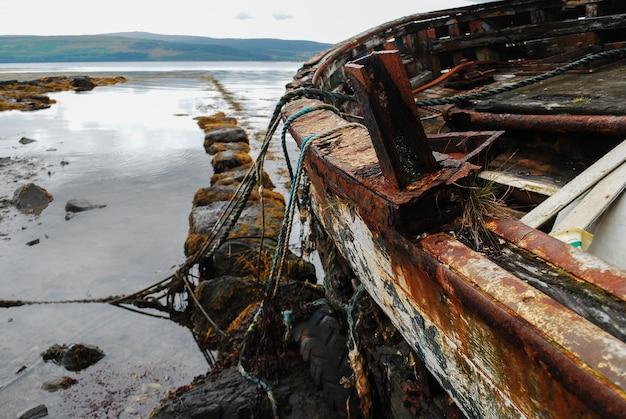 해안가에 있는 오래된 녹슨 보트의 근접 촬영