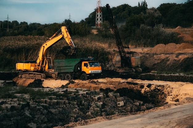 放棄された土地にトラックとブルドーザーを備えた進行中の建設のクローズアップショット