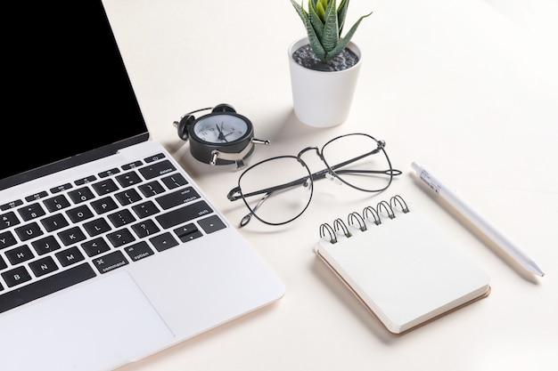開いているノートパソコン、メガネ、植物、ペン、メモ帳、目覚まし時計のクローズアップショット
