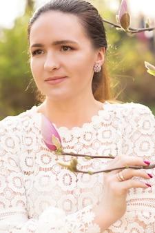 咲くモクレンの花の近くでポーズをとってヌードメイクで魅力的なブルネットモデルのクローズアップショット