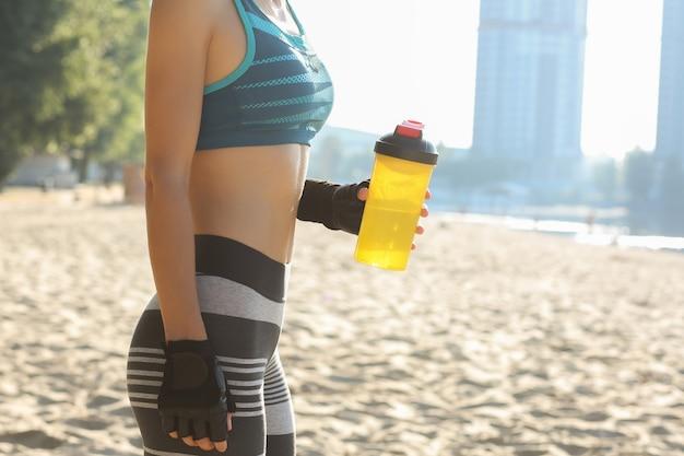 ビーチでポーズをとって水筒を持って、スポーツフォームを持つ魅力的な女性のクローズアップショット。テキスト用のスペース