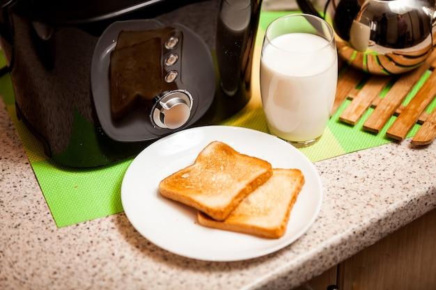 Снимок запеченных тостов на белом блюде со стаканом молока крупным планом