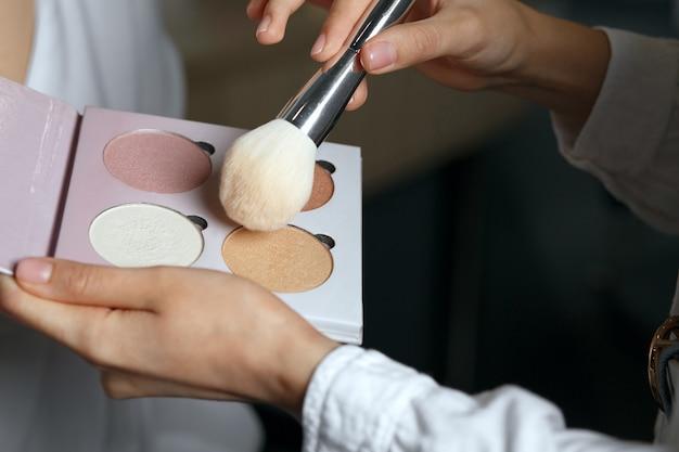 蛍光ペンパレットと自然なブラシを使用して、女性に化粧をする美容師のクローズアップショット