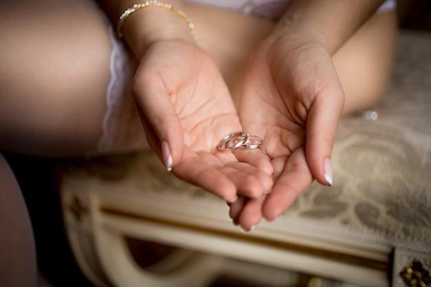Снимок крупным планом красивой невесты в нижнем белье, держа в руках обручальные кольца