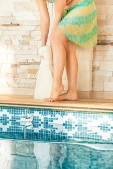 スイミング プールでタオルで足を乾かす美しい女性のクローズ アップ ショット