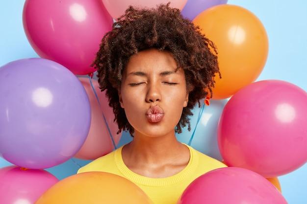 誕生日のカラフルな風船に囲まれてポーズをとって美しい若い女性のクローズアップショット