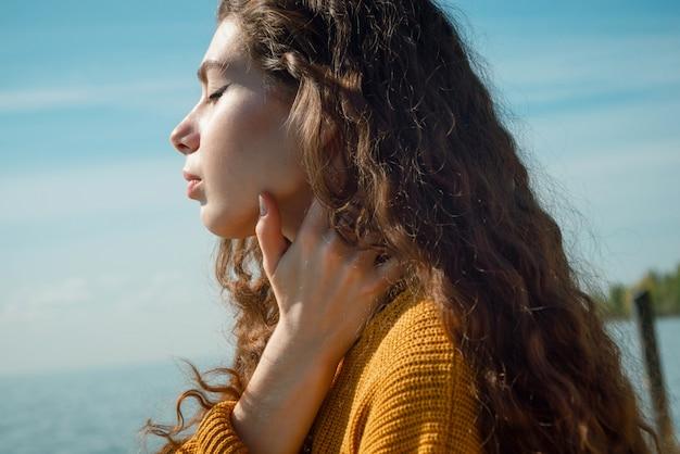 ビーチで黄色いセーターを着ている巻き毛の美しい若い女性のクローズアップショット、選択的な焦点
