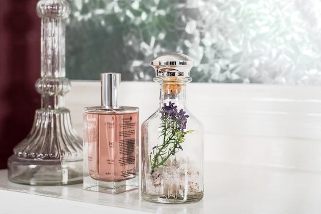 Снимок крупным планом стеклянных бутылок красивой формы, наполненных духами