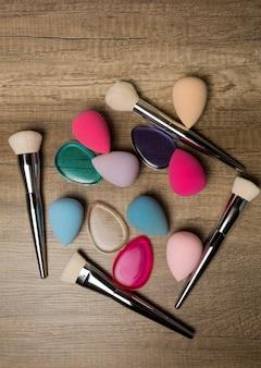 Снимок крупным планом косметических блендеров, силиконовых губок и кистей для макияжа на деревянном фоне. место для текста