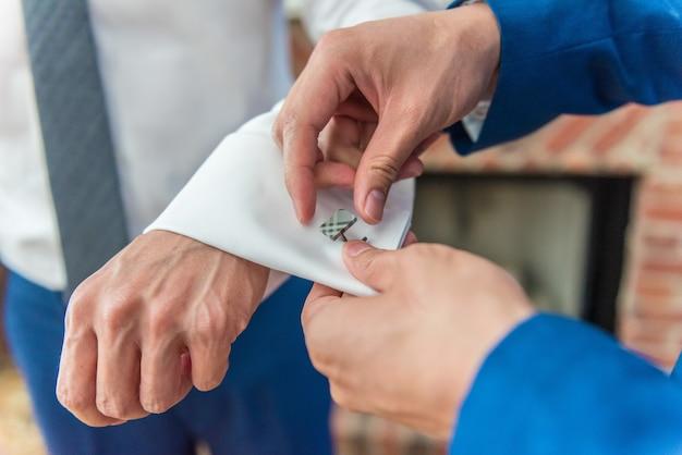 ボタンカフスボタンで新郎を助ける最高の男のクローズアップショット-結婚式の日のコンセプト