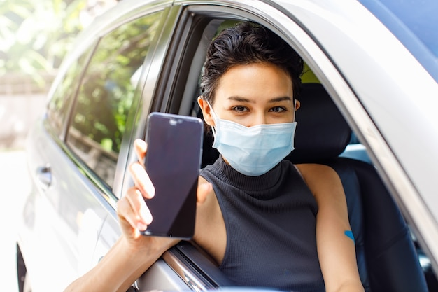 コロナウイルスワクチン接種のためのドライブスルーラインで車に座っているフェイスマスクを身に着けている女性の手のアプリケーション予約登録コピースペースのための空白の画面の携帯電話のクローズアップショット。
