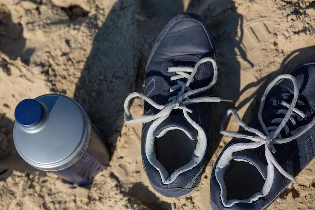 砂の上に立っている青い女性のスニーカーと水のボトルのクローズアップショット
