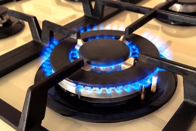 国内のキッチンストーブから青い火のクローズアップショット。燃える炎プロパンガスのガスコンロ。