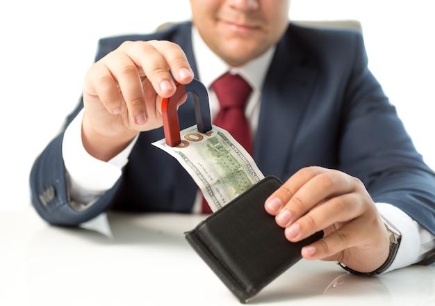 磁石で財布からお金を盗むビジネスマンのクローズアップショット