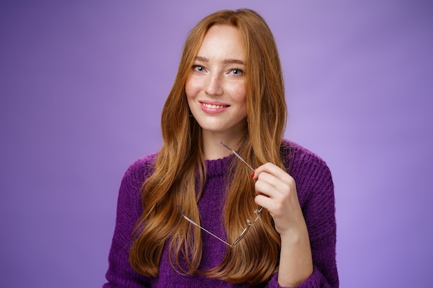 Снимок крупным планом очаровательной нежной и милой рыжей женщины в фиолетовом свитере, держащей очки и улыбающейся ...