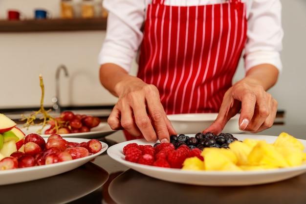 Снимок крупным планом руки шеф-повара положить кусочки фруктов во вкусный вкусный вкусный сладкий смешанный фруктовый салат в белой миске на кухонном столе. концепция органической и натуральной здоровой пищи.