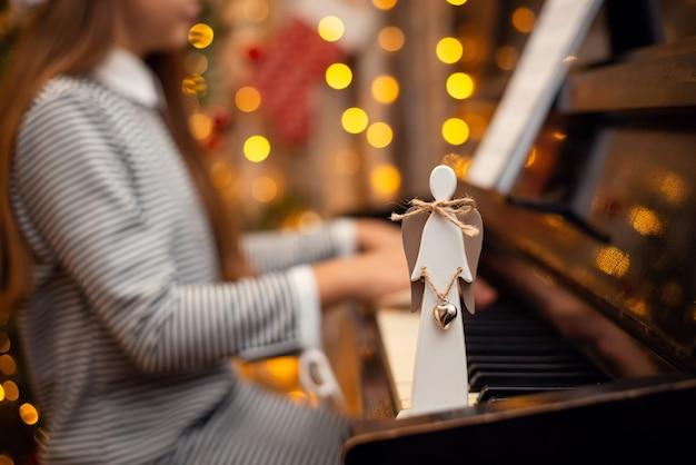어린 소녀가 연주하는 동안 피아노에 크리스마스 천사의 근접 촬영 샷