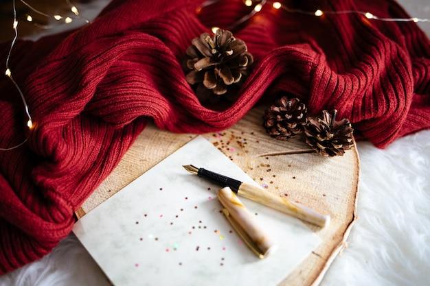 빨간색 패브릭에 크리스마스 트리 범프와 반짝이는 별 스티커가있는 펜의 근접 촬영 샷