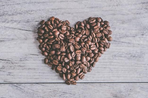 회색 나무 배경에 심장 모양의 커피 콩의 근접 촬영 샷