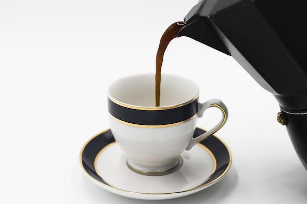 흰색 표면에 고립 된 주전자에서 컵에 붓는 커피의 근접 촬영 샷