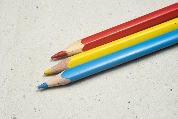 Крупным планом выстрелил красочные карандаши на шероховатой поверхности