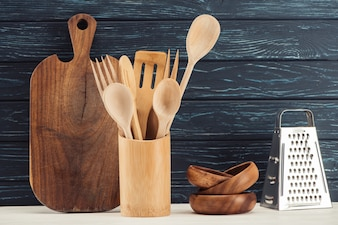 Closeup shot of cutting board, kitchen utensils, grater and ramekins in front of wooden wa