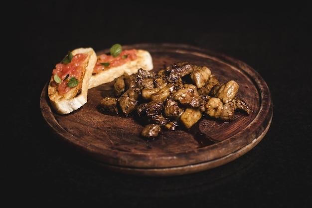 Крупным планом снимок вкусного жареного мяса на деревянной тарелке, изолированной на черном столе