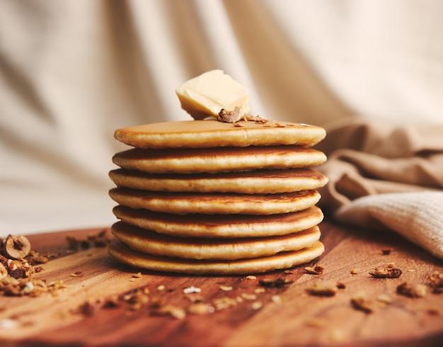 버터, 무화과, 나무 접시에 구운 견과류와 함께 맛있는 팬케이크의 근접 촬영 샷