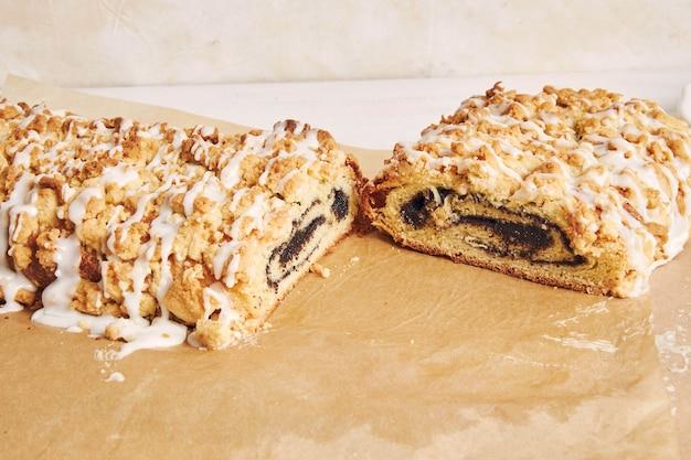 白いテーブルの上に白い砂糖釉薬とおいしいケシの実のケーキのクローズアップショット